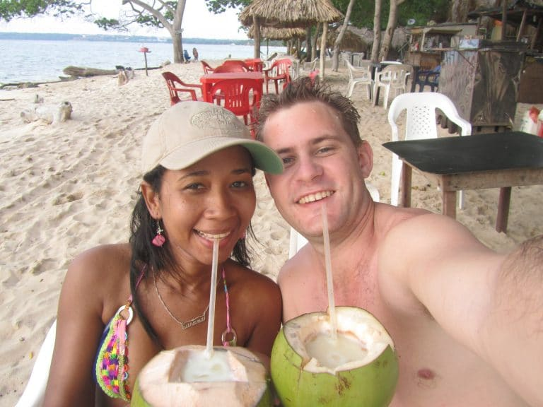 Photo of Adam and Susana drinking a drink out of a coconut at the beach.