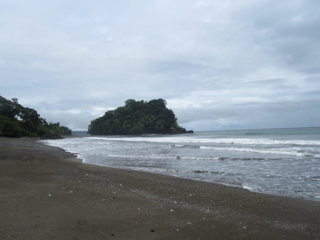 Photo of the beach at Nuquí Colombia with a small tree covered island in the background.