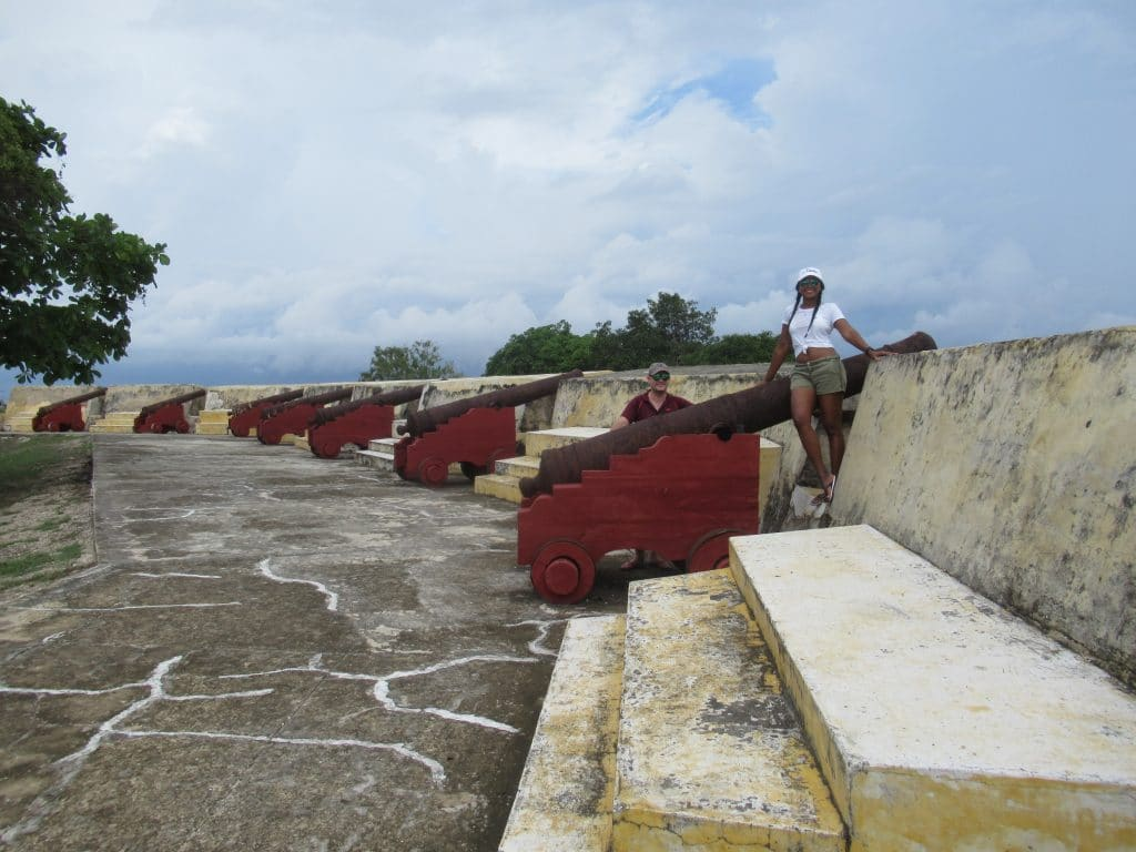Susana and Adam posing with a cannon with others in the background at the El Angel San Rafael Fort