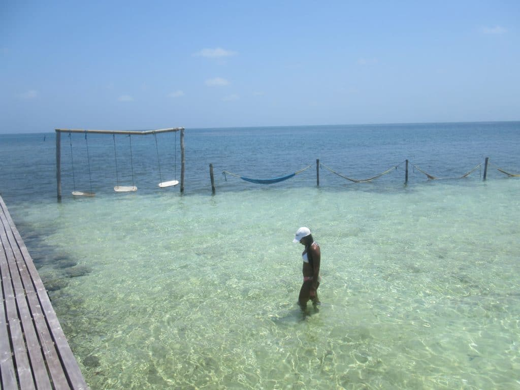 Photo of a girl standing in the crystal clear water of Isla Roots Hostel back swimming area.
