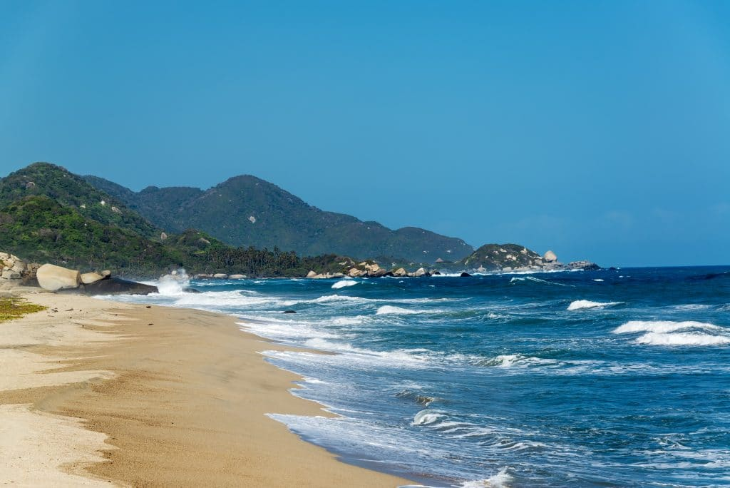 Photo of waves washing up on a beach in Tayrona Colombia