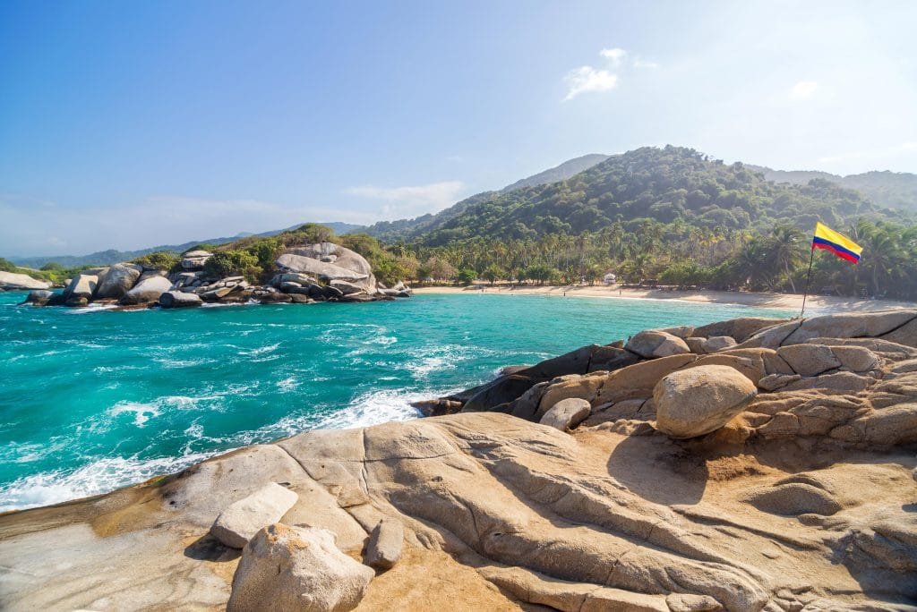 Photo of rocks overlooking the Caribbean sea at Tayrona National Park with a Colombian flag flying over them.