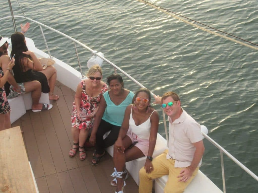 Photo of people sitting on a boat, the man on the right wearing the RAWWOOD Bamboo sunglasses
