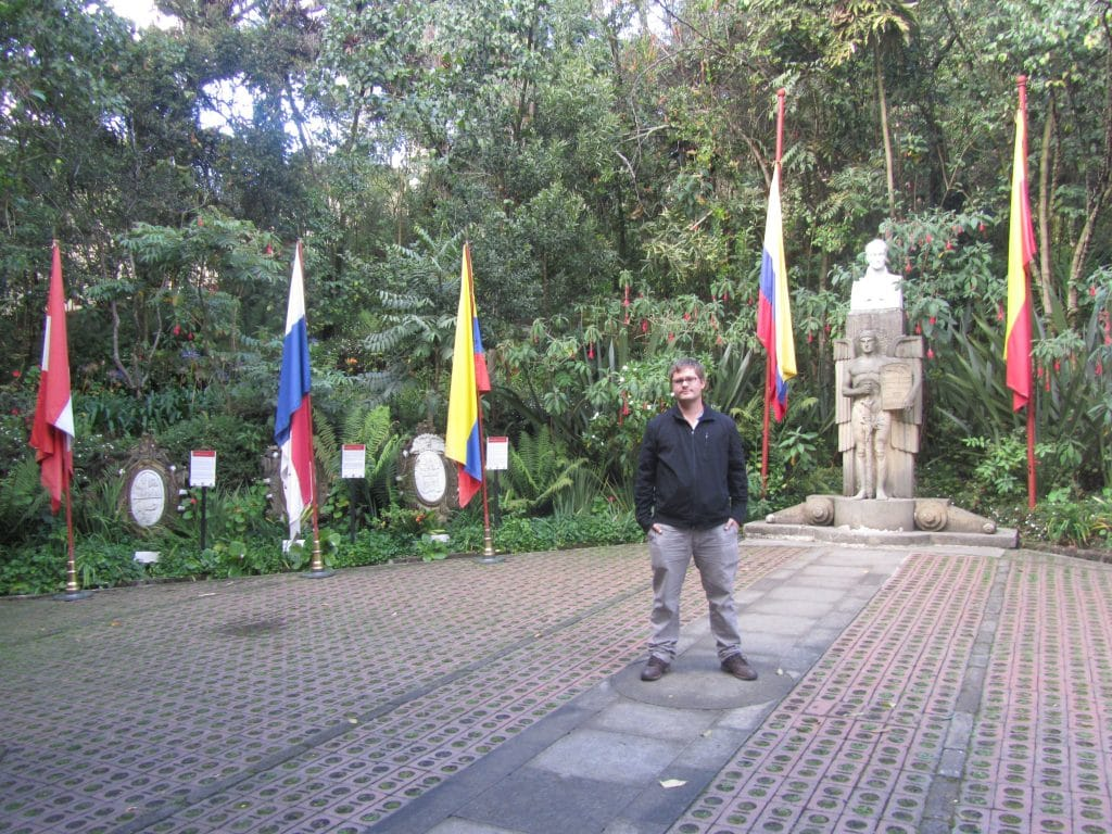 A guy standing in a plaza with the flags of different countries at the Quinta de Bolívar