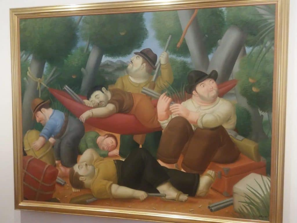 Photo of a painting depicting a group of guerillas camping at the Botero Museum.