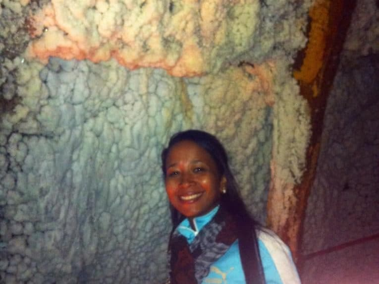 A girl standing in front of a salt formation in the salt cathedral in bogotá.