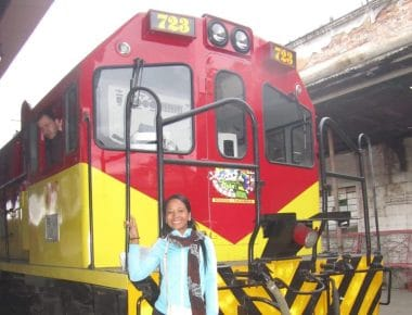 A girl standing on the train engine on the train in Bogotá.