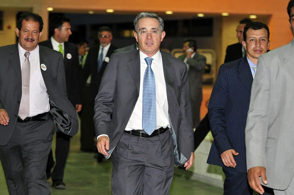 Photo of Alvaro Uribe walking with others in suits.