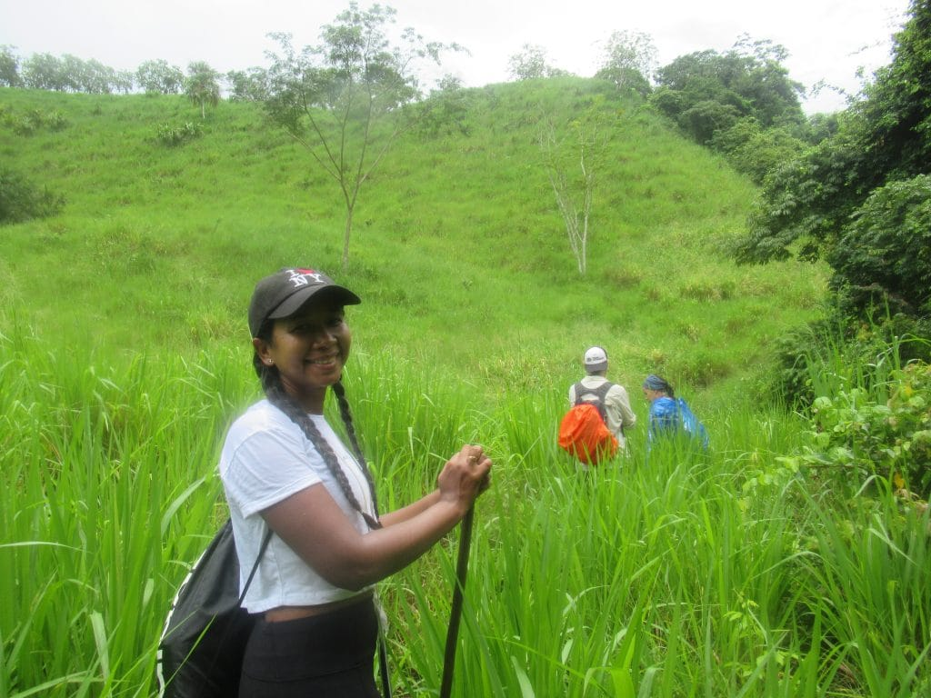 Photo of Susana with others walking in the background in a green grassy hill.