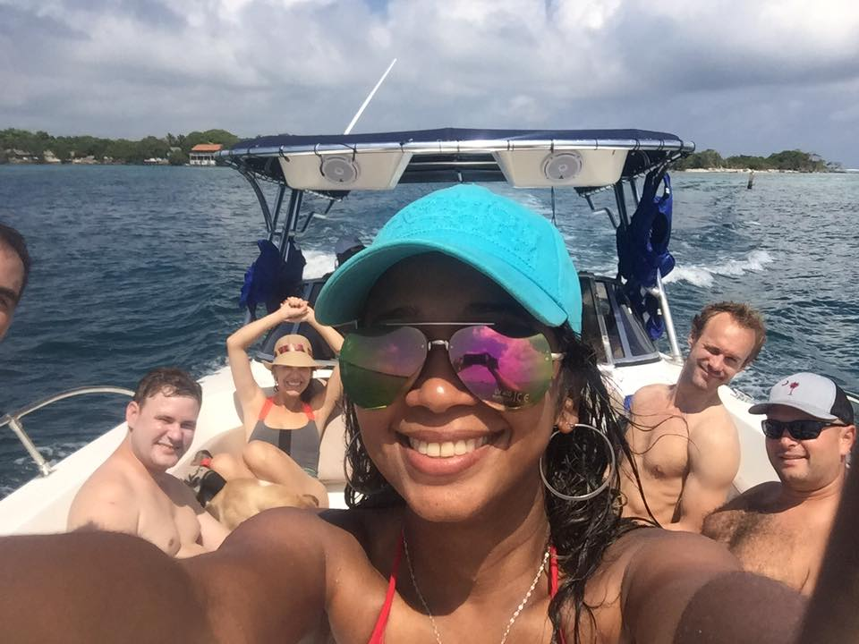 Photo of a girl taking a selfie with others on a boat to the Rosario Islands behind her.