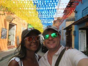 Photo of a girl and guy in the street of Cartagena, Colombia with Colombia flag pennants above.