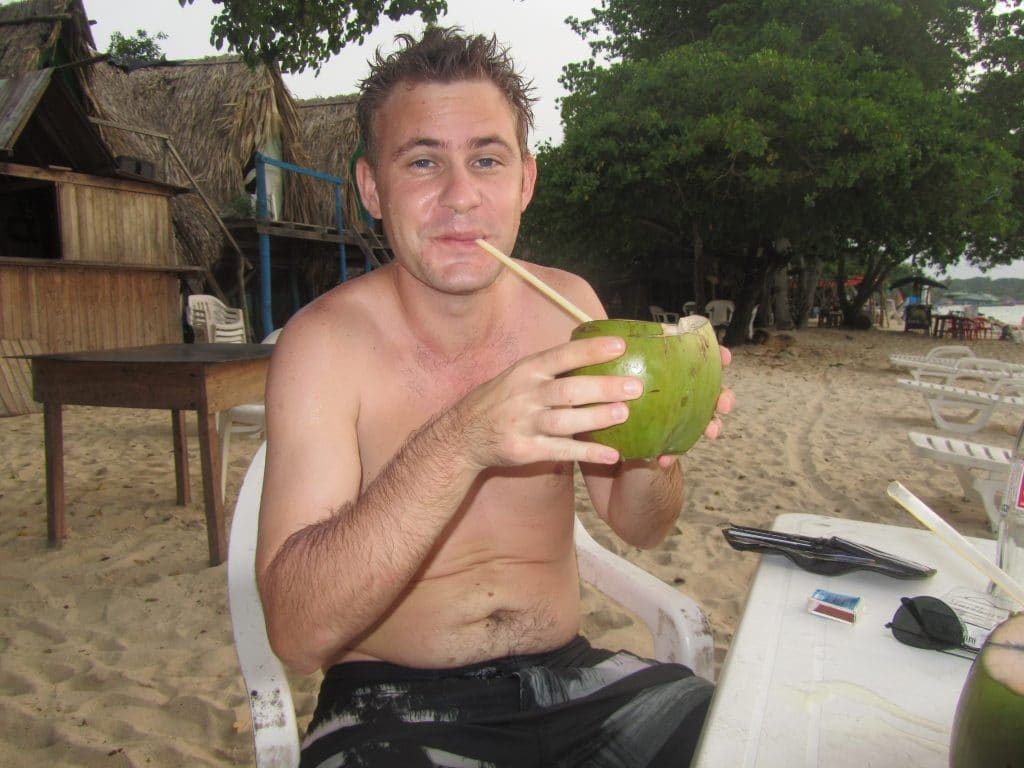 Photo of a guy drinking out of a coconut at Playa Blanca, Barú.