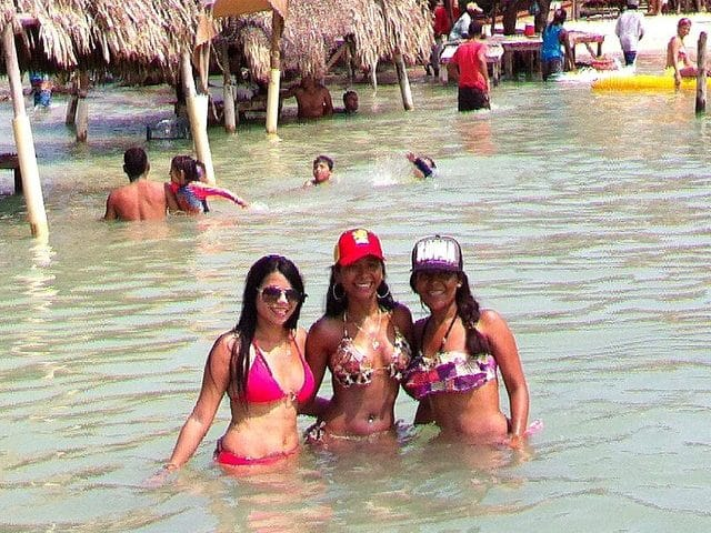 Photo of 3 girls standing in the water at Cholón in the Rosario Islands.