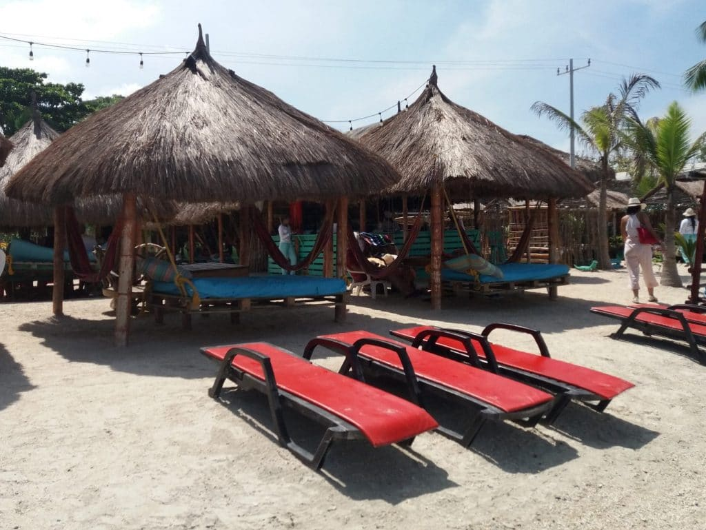 Photo of some beach huts with chairs in front of them at Bomba Beach, Cartagena