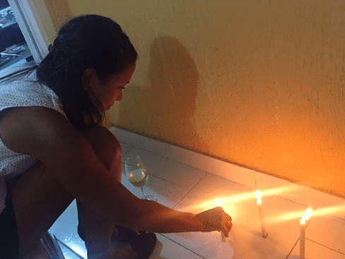 Photo of a girl lighting a candle on the Día de las Velitas