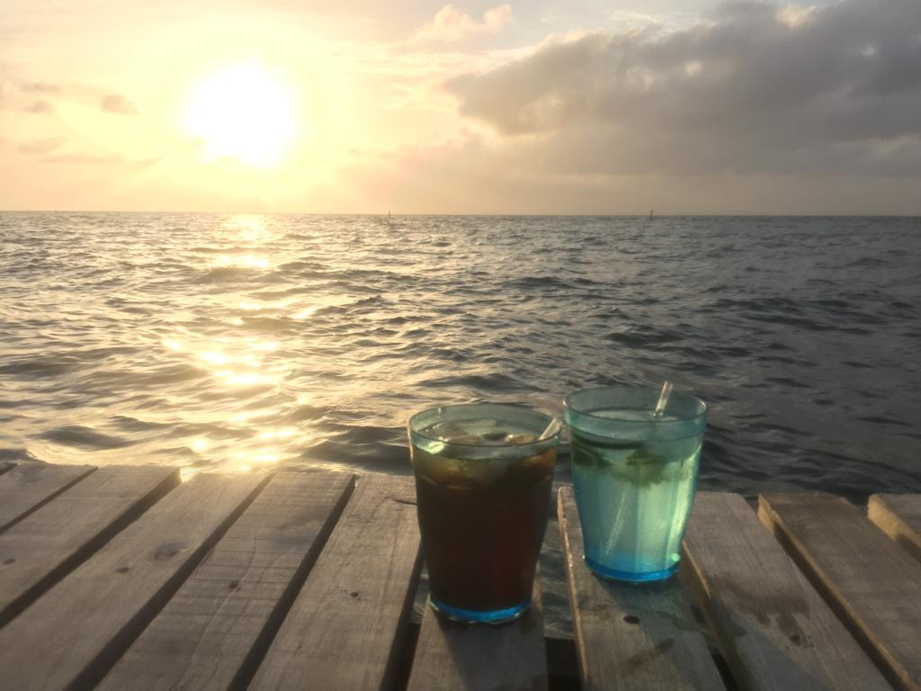 Photo of two cocktails with the sun setting over the water in the Colombia San Bernardo Islands in the background