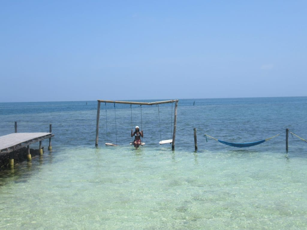 Photo of a girl on a swing set in the water of Tintipán Island.