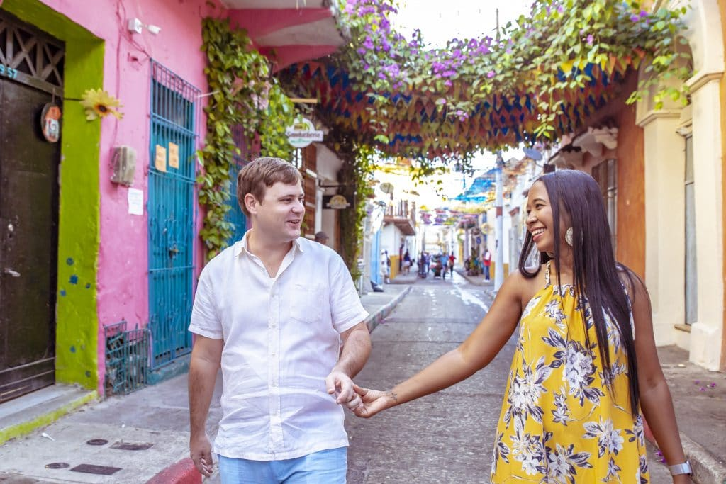 Photo of Adam and Susana walking down a street in Getsemaní during their photo session with Marina Maldonado