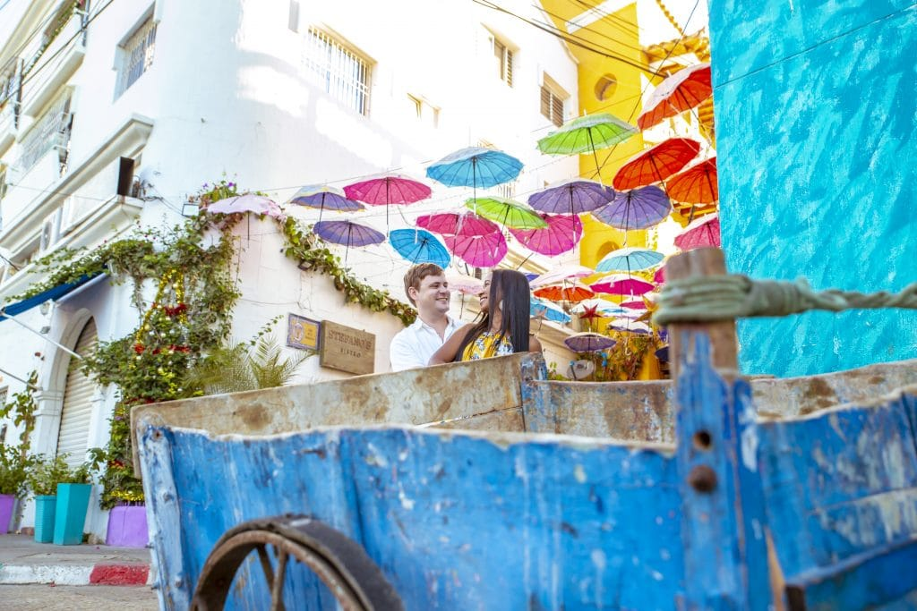 Photo of Adam and Susana with the cart in front of them and colorful umbrellas hanging above the street behind.
