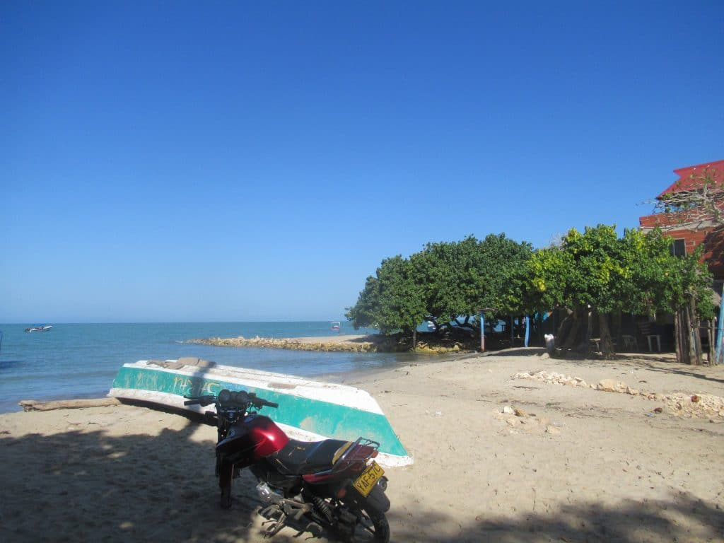 Photo of the beach in Rincón del Mar, Colombia, with a boat and motorcycle in the foreground.