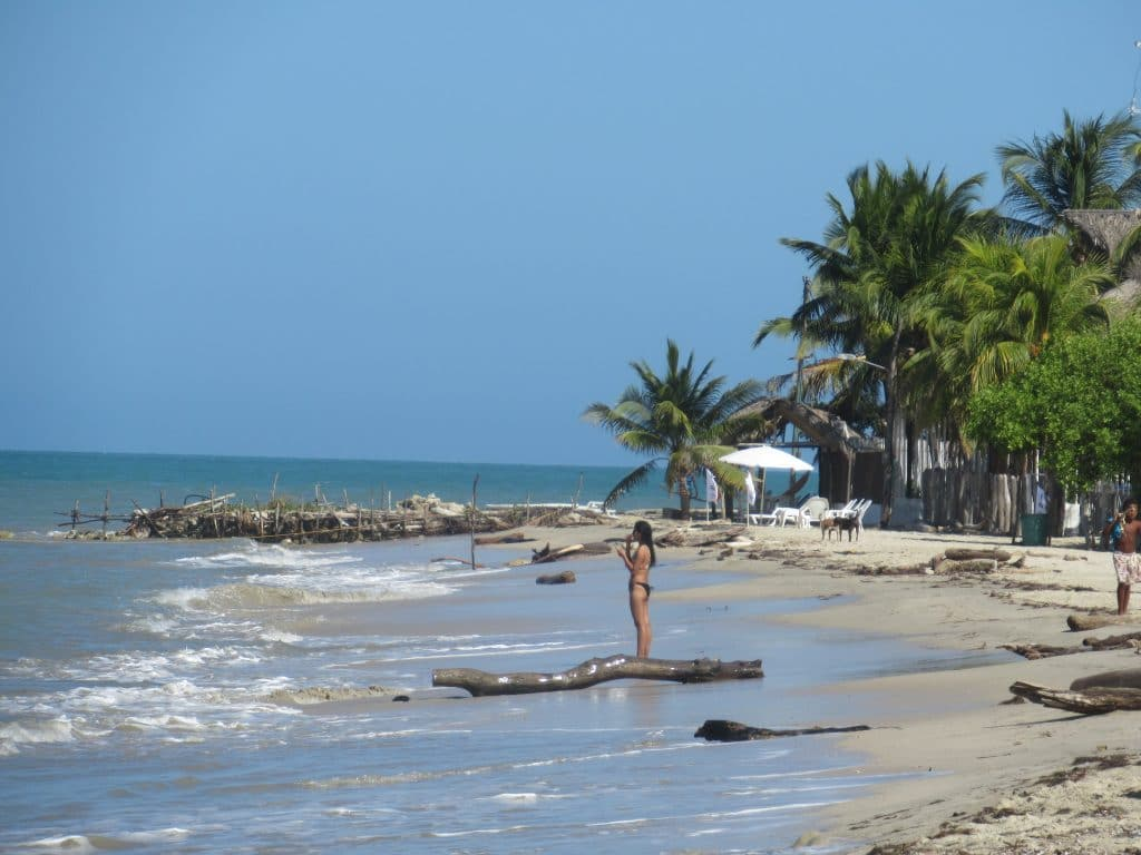 Photo of the Beach in Rincón del Mar, Colombia with a few people standing on it.