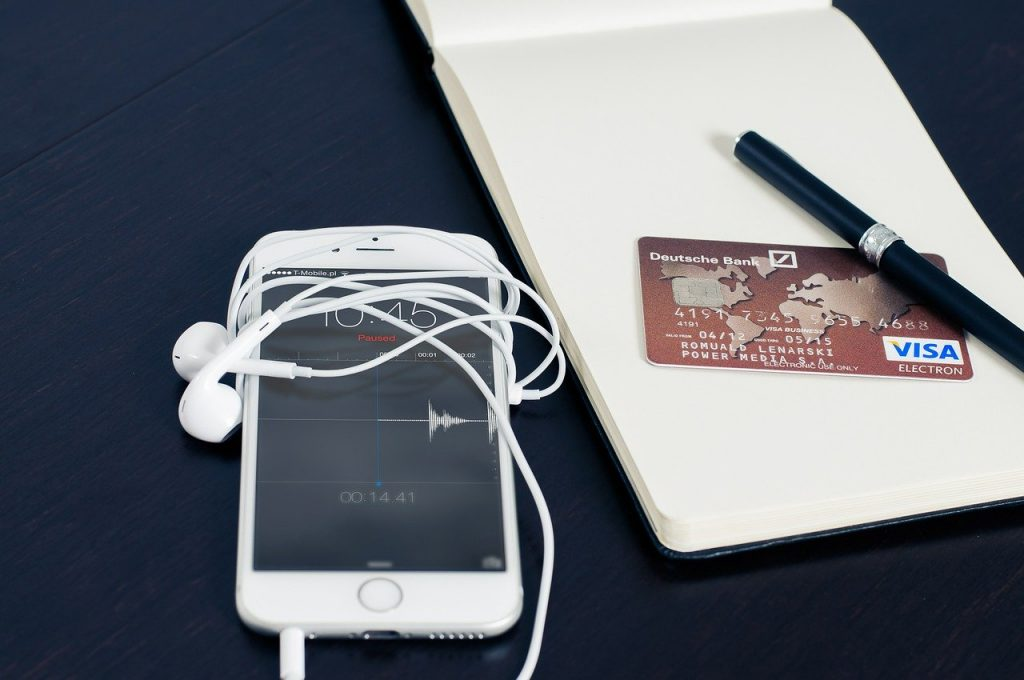 Photo of a phone beside a pen and pad with a credit card from someone possibly managing their online bank account for a frequent traveler.
