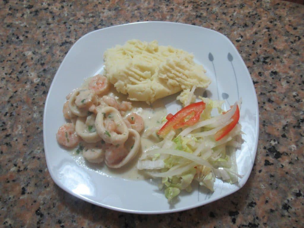 Foto de la receta de calamares y camarones al ajillo servido en el plato.