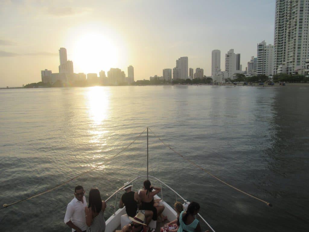 Foto del atardecer atras de unos edificios en frente de algunos personas sentados en el frente de un bote.