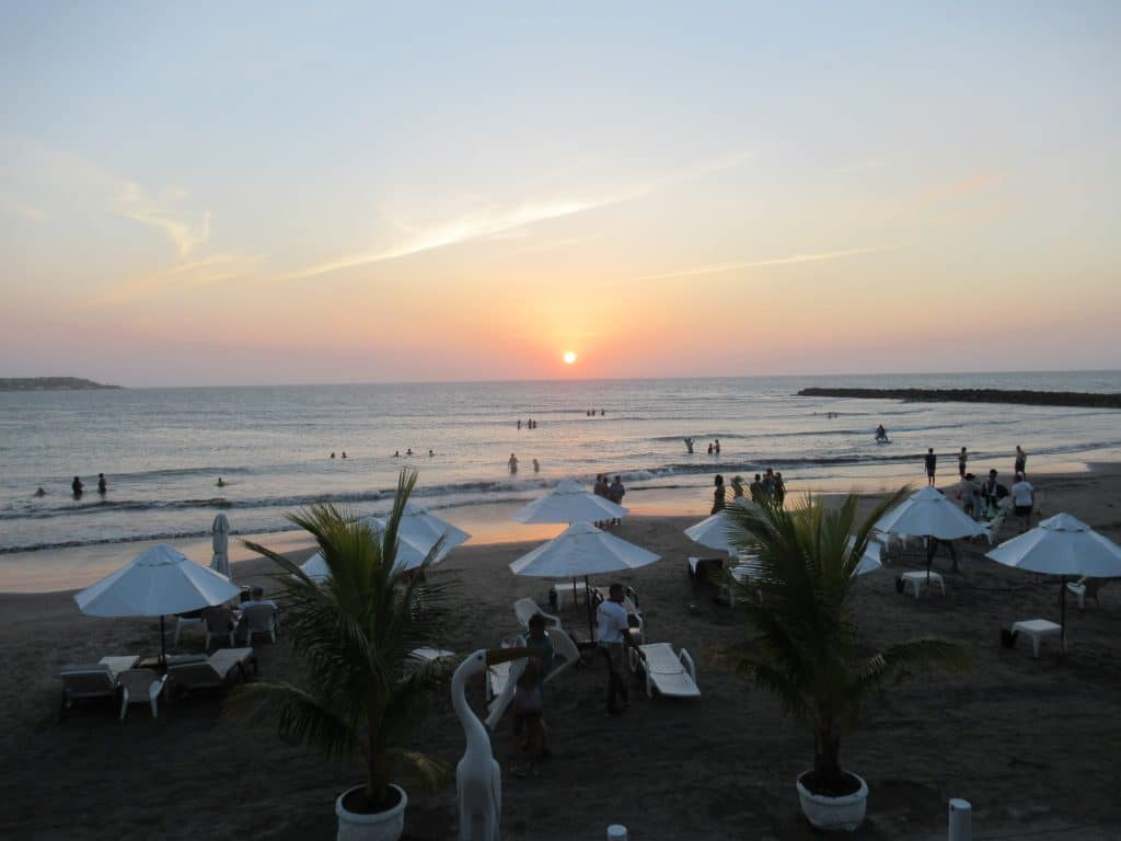 Photo of a Cartagena beach with chairs, umbrellas, and people with the sun going down.