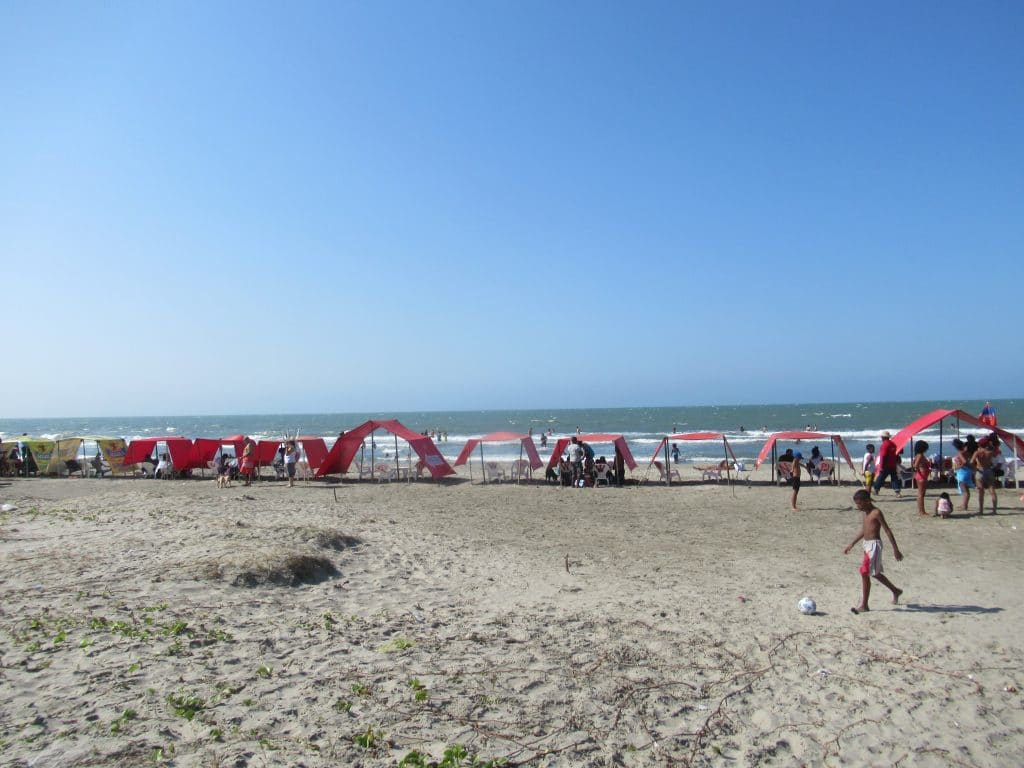 Photo of the Marbella beach in Cartagena with shade tents and some people in the background.