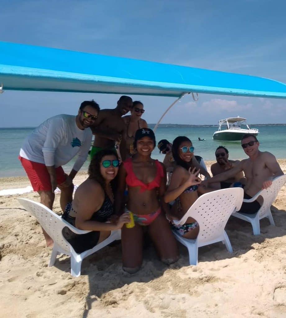 Foto de algunas personas en la playa con el mar atras.