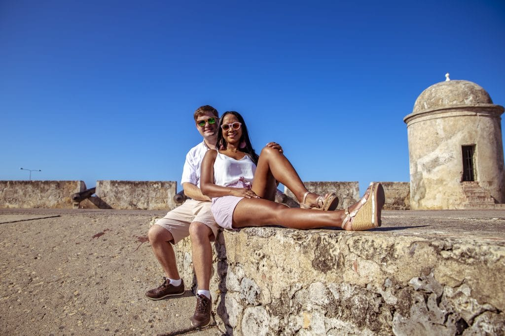 Photo of a couple sitting on the wall in Cartagena.