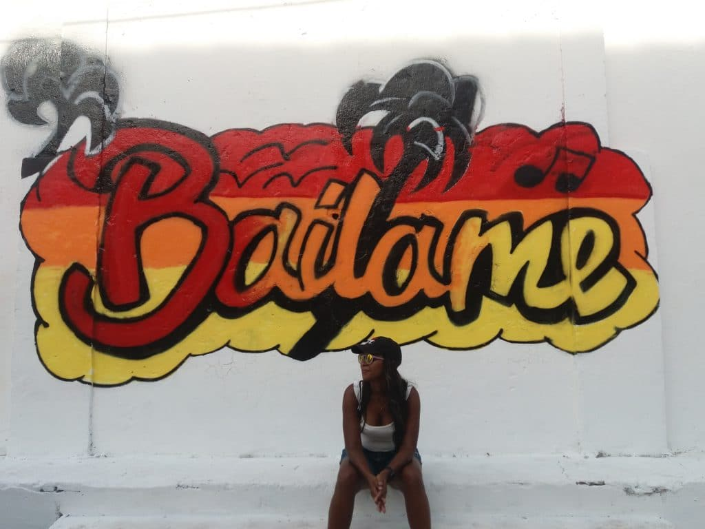 A girl sitting in front of graffiti in Getsemaní.