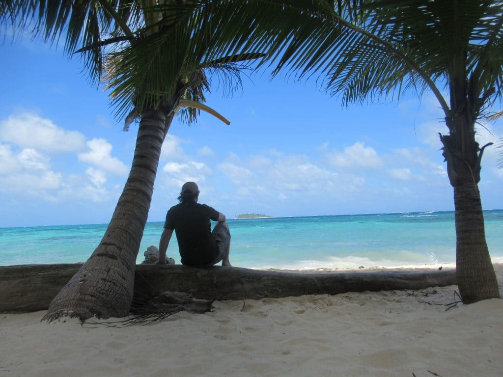 Photo of a person sitting on a beach between two palm trees looking over the water of a Colombia San Andres Island.