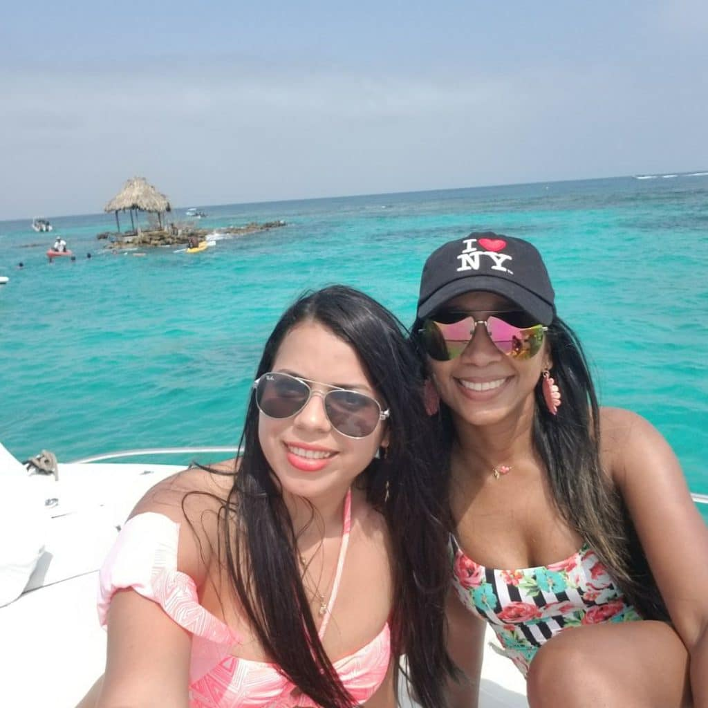 Photo of two girls on a boat in the Cartagena Rosario Islands with the water in the background.