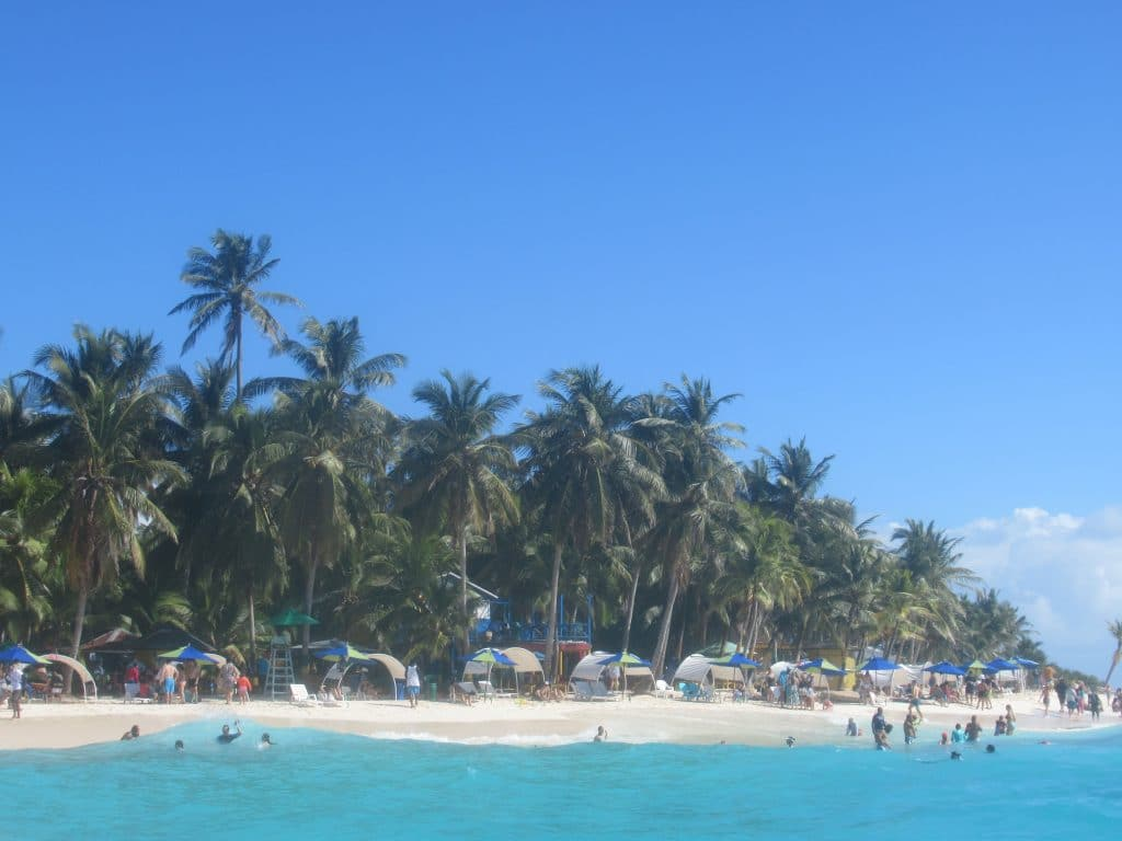 Photo of the beach front with people on the beach and palm trees behind on Johnny Cay, one of the best beaches on San Andres Isla.
