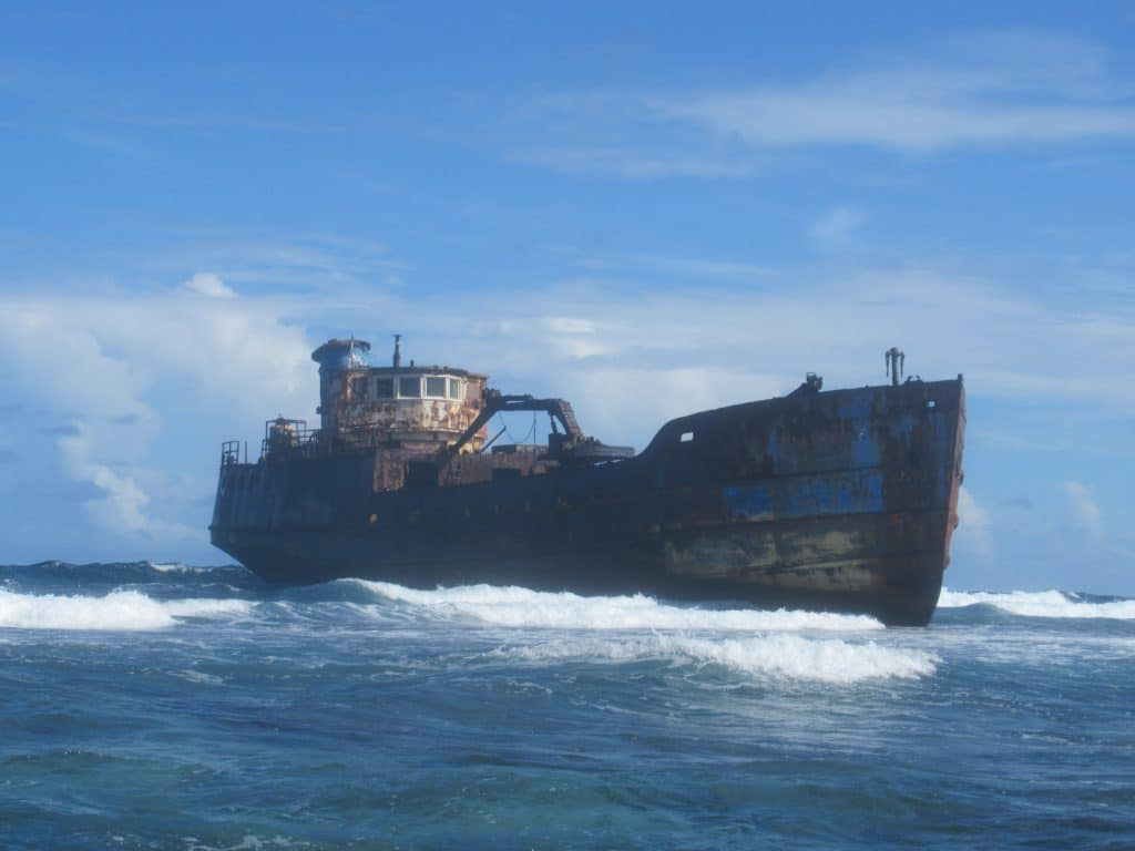 Photo of a rusted ship with waves crashign around it.