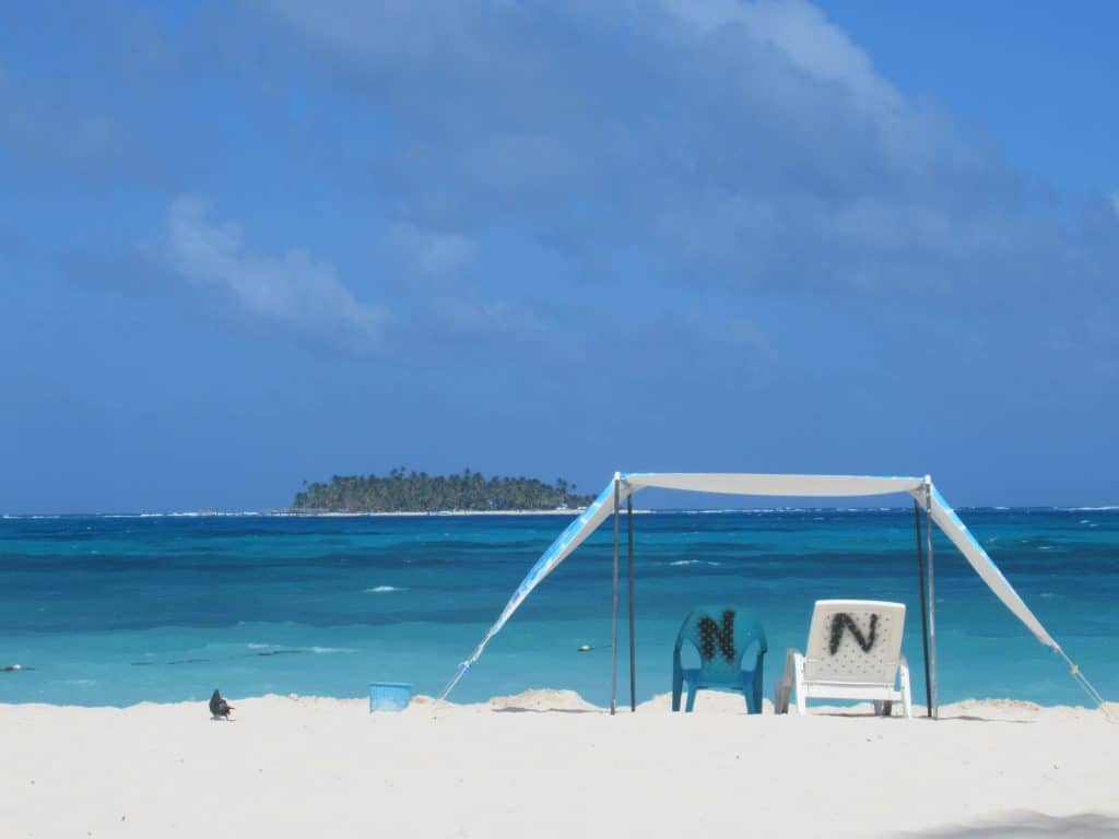 Photo of two empty chairs under a shade tent on one of the best beaches of San Andres Island, with a small island in front.