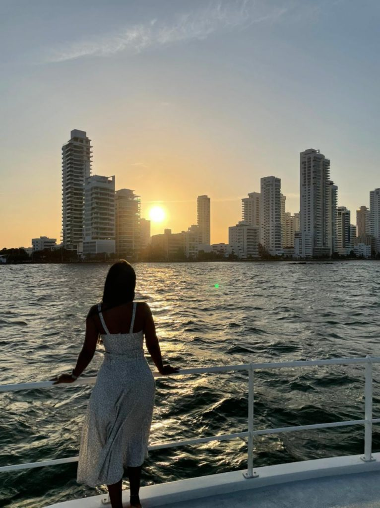 Photo of a girl watching the sunset from the deck of the San Juan Catamaran in Cartagena.