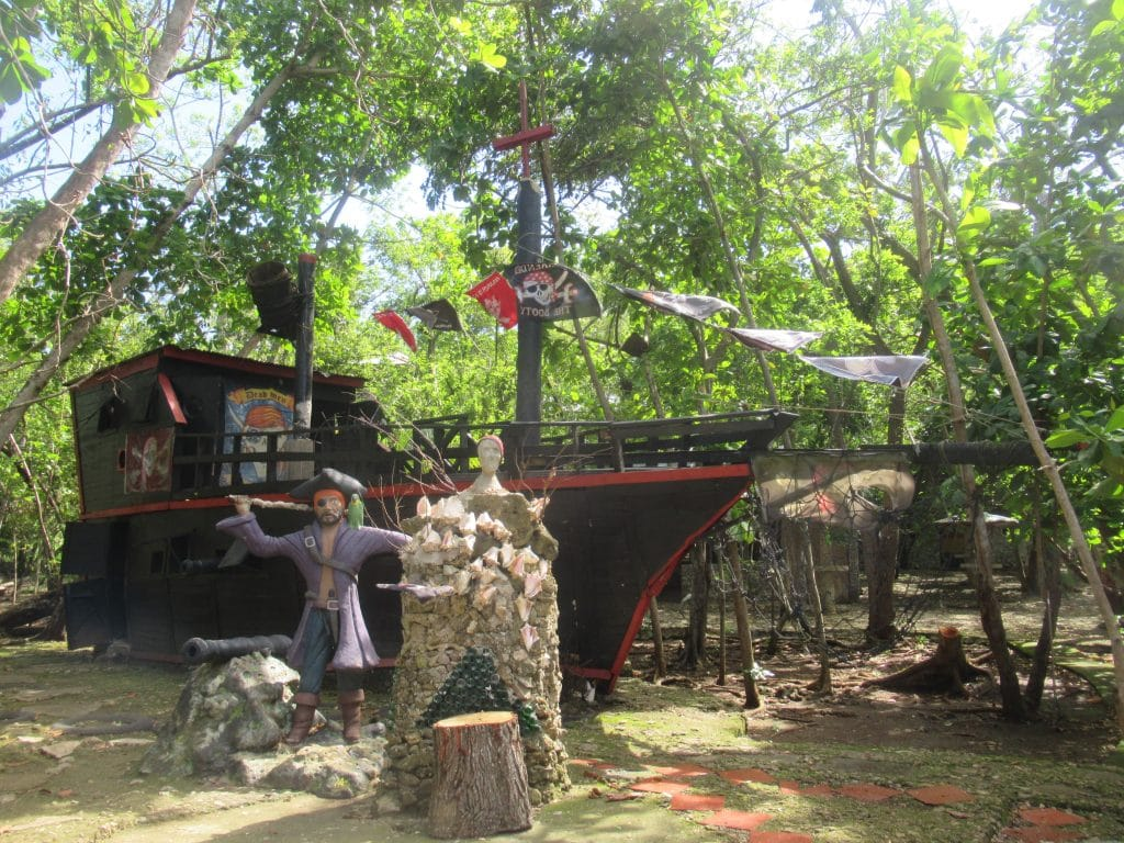 Photo of a model pirate ship with a figure in front of it at Morgan's Cave on San Andres Isle in Colombia.