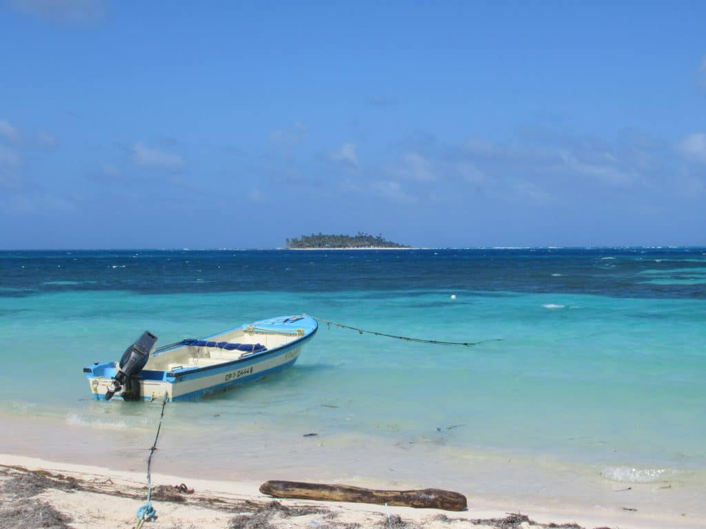 Photo of a boat tied off just off the beach of San Andres with an island out in front off the coast.
