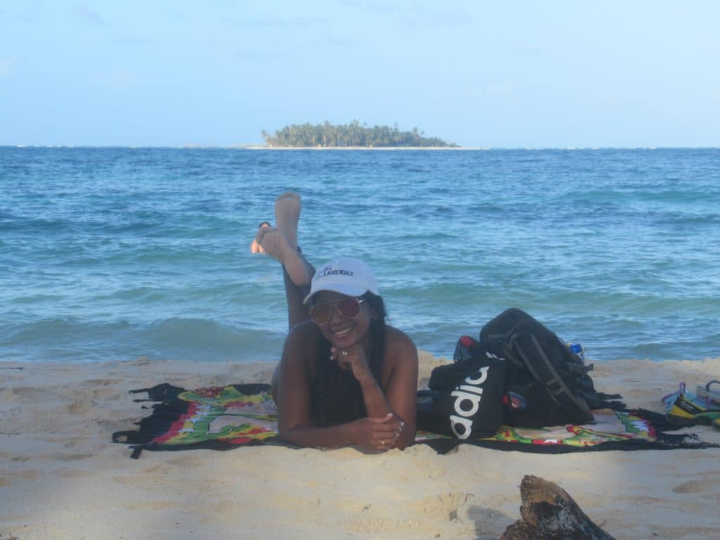 Photo of a girl on the beach in San Andres Island with an island in the water behind her.