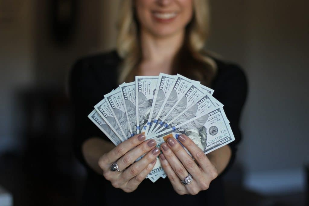 Photo of a woman holding 100 dollar bills like you might get if you cash you second stimulus check living abroad.