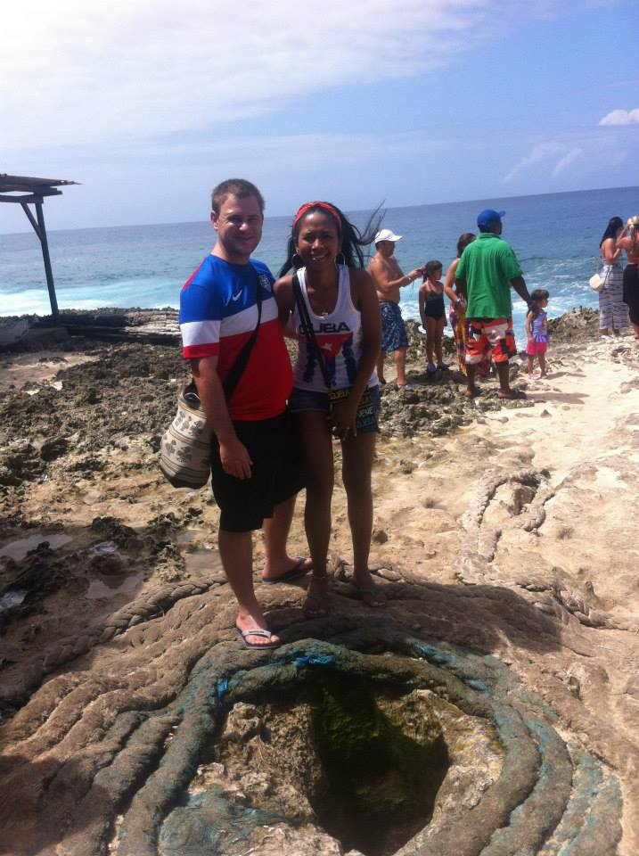 Photo of a couple standing over the hole of Hoyo Soplador on San Andres.