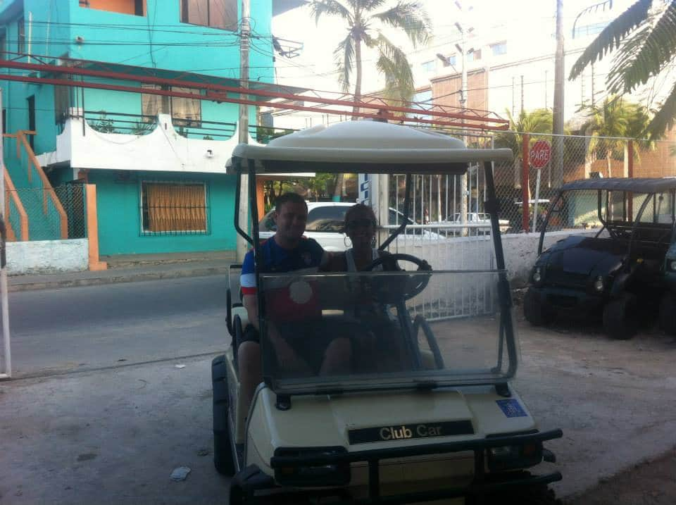 Photo of a couple in an old golf cart in San Andres.