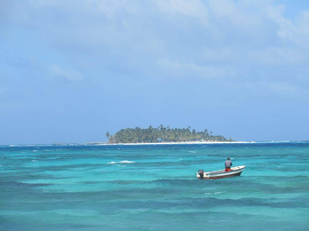 Photo of a boat floating in the water with Johnny Cay in the background from the beach in San Andres Island, Colombia.