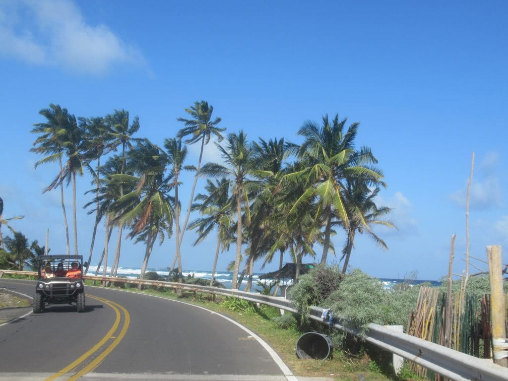 Photo of a road on San Andres with the beach on one side and a golf cart passing coming the opposite way.