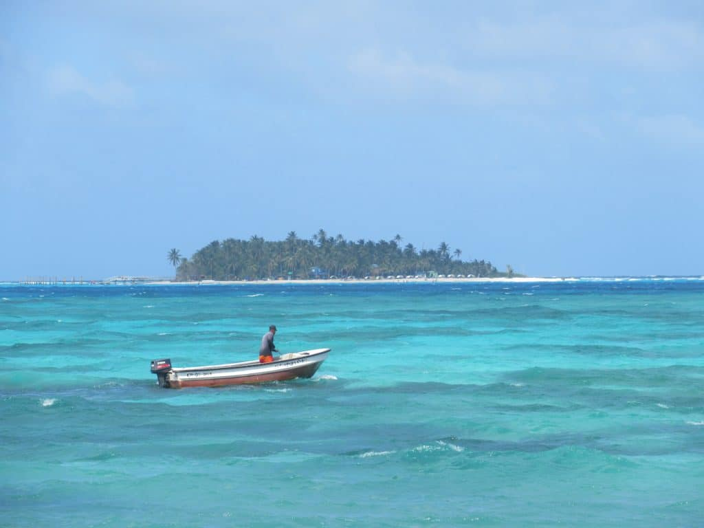 Photo of Johnny Cay, another one of the best beaches in San Andres, from a distance, with a boat floating in the foreground.