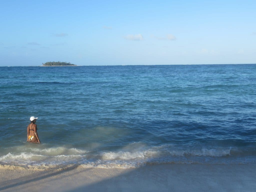 Photo of a girl wading in the water looking out at Johnny Cay in the distance.