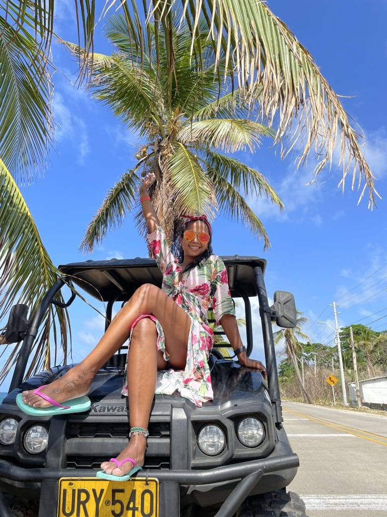 Photo of a girl sitting on the hood of a golf cart in San Andres.